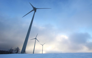 An image of a wind turbine  jutting out of a snowy landscape.