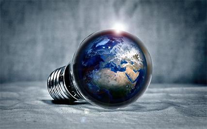 An edited image of the Earth encapsulated within a lightbulb, reflecting the connection between the Earth and energy savings.