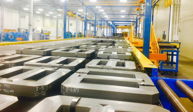 Corefficient's brightly lit electrical transformer core manufacturing plant in Monterrey, Mexico, showcasing countless quality transformer cores neatly placed on the assembly line.