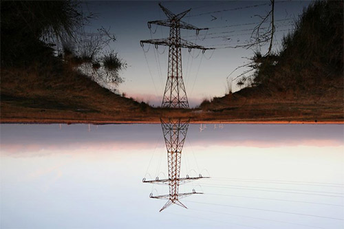 A large power line tower, with its reflection being beautifully mirrored in a nearby body of water