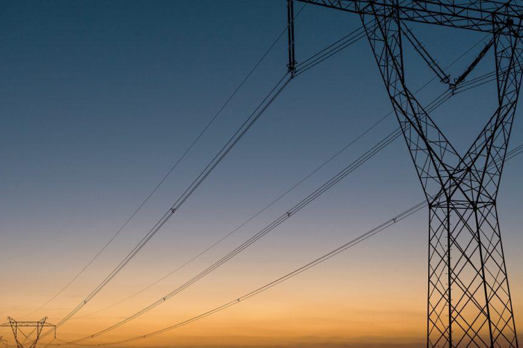 Sky at dusk with an electrical tower in the foreground joined to another that is in the background by electrical wires.