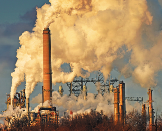 A fossil fuel production plant—orange towers with plumes of smoke pouring out, an electrical grid in the background, against a blue sky.