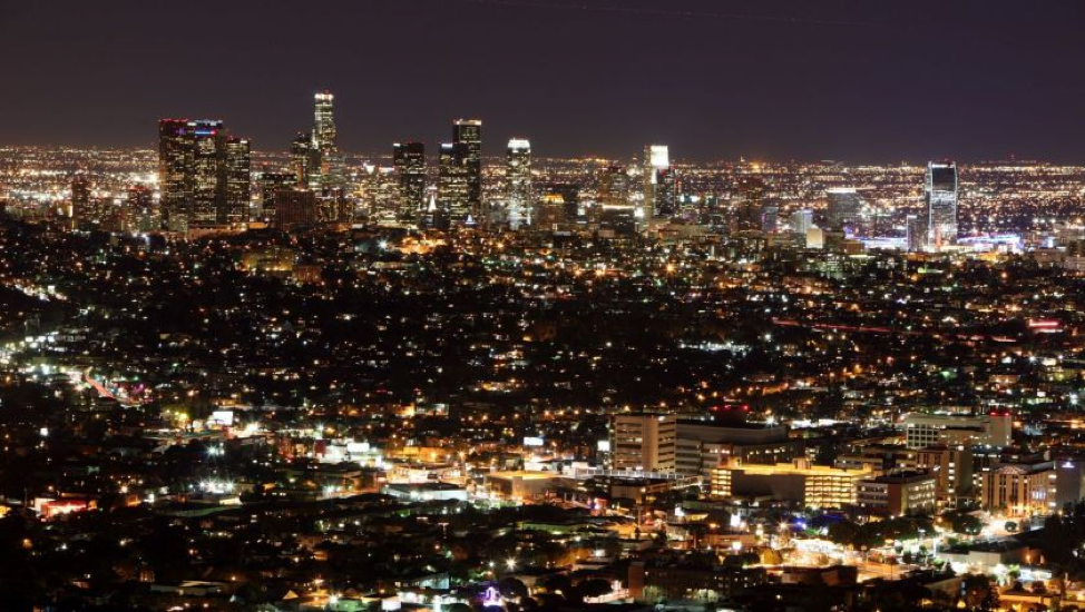 A view of downtown Los Angeles at night. The city is aglow with electrical light all the way to the horizon line.