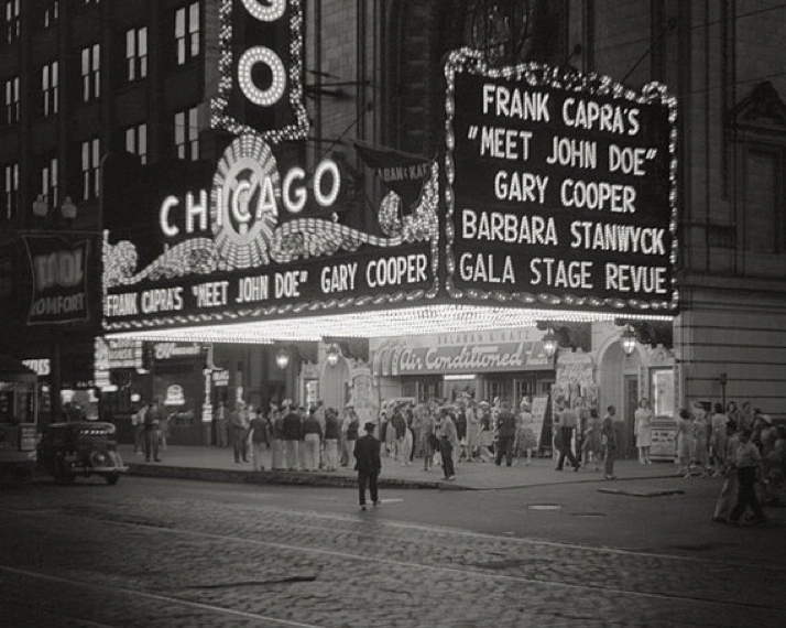 "A black and white picture of The Chicago Theater at night, with a lit-up marquee that reads: ""Frank Capra's 'Meet John Doe' Gary Cooper, Barbara Stanwyck, Gala Stage Revue. (1941)"