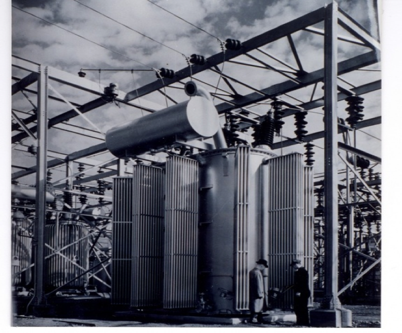 Two men standing in front of the transformer at Silver Lake Substation, the old General Electric Company, which Stanley began.
