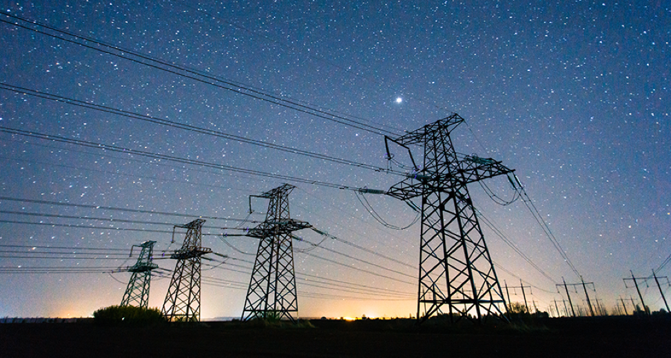 An AC electric grid at sunset: the landscape, grids, and wires are black, the yellow sun sets behind the horizon, and the night sky is above, filled with stars.