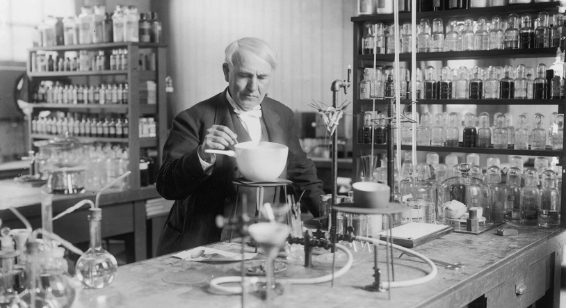 A sepia-toned photograph of Edison tinkering around in his laboratory. Dressed in a fancy, old-fashioned      suit, he stands behind a long table with a vintage chemistry set, and behind him are shelves of various chemicals in small glass bottles.