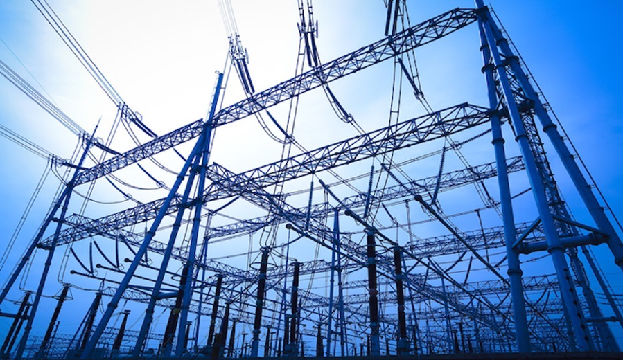An electrical transformer grid, with many poles and wires, beneath a blue sky and white light overhead.