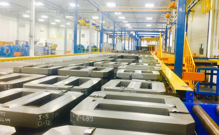 Corefficient's electrical transformer core manufacturing line in Monterrey, Mexico. Close angle on multiple transformer cores in a brightly lit factory environment.