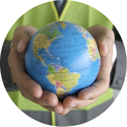 A close-up picture of a worker wearing a neon yellow vest holding a small globe with North and South America facing the camera in the palms of his hands.