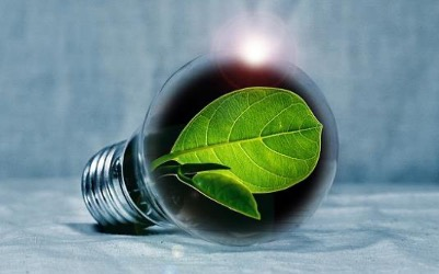 On a pale blue background, a close-up of a digitally rendered, realistic-looking glass lightbulb with a green leaf inside and the sun coming up over the top of the bulb like on a horizon.