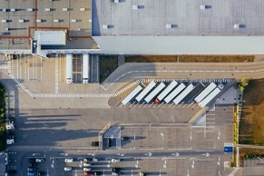 A birds-eye view of a large factory, a large parking lot, and trucks lined up in front waiting to be loaded at the docking bays or in long parking spaces.